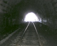 black and white tunnel with railroad tracks