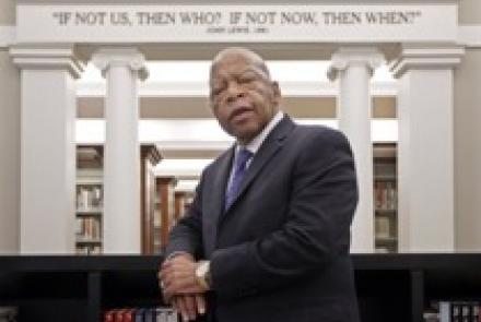 John Lewis leaning against a book case