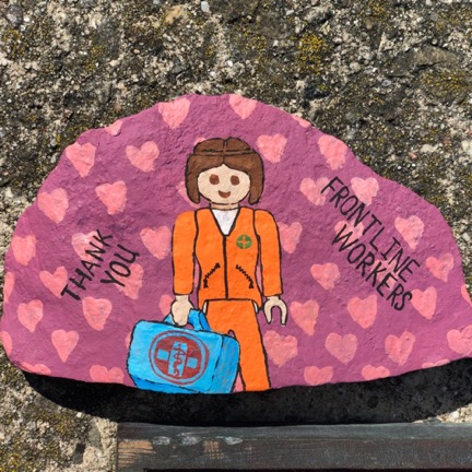 rock painted pink with pink hearts of a female medical worker dressed in orange saying thank you front line workers