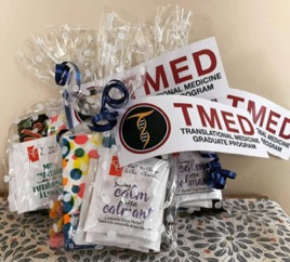 care packages for students wrapped in cellophane tied with a ribbon and a TMED logo table