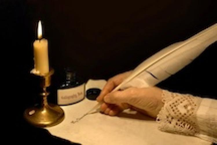 female hand using a feather scribe to write on paper by candelight
