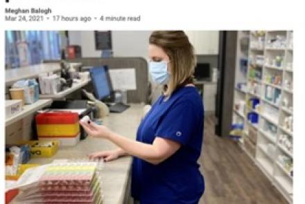 pharmacy worker looking at a pill bottle